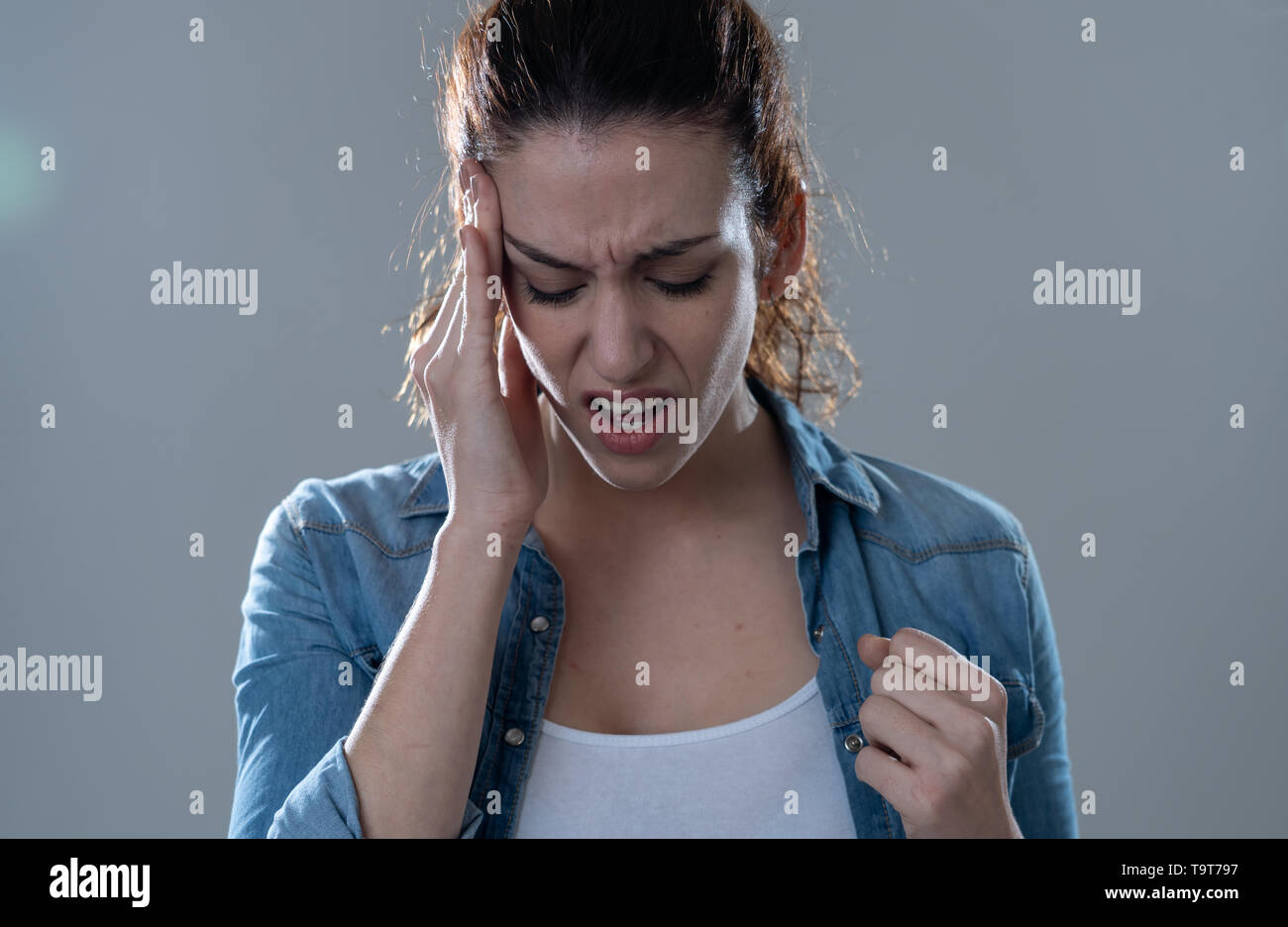 Close up portrait of a young woman looking worried and thoughtful suffering from migraines in great pain. Isolated on neutral background. In facial ex - Stock Image