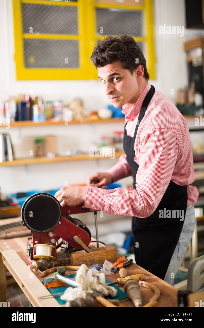 Focused joiner working on machine in professional carpentry shop - Stock Image