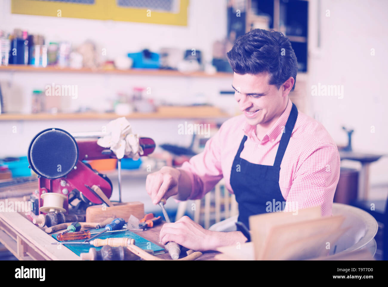 Skilled concentrated joiner working in workshop with chisel in hands - Stock Image