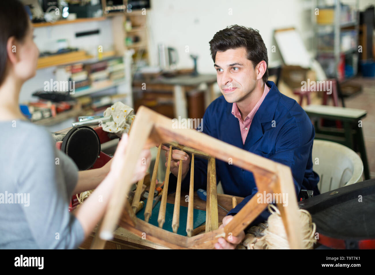 Polite master carpenter taking from young woman broken chair for repair - Stock Image