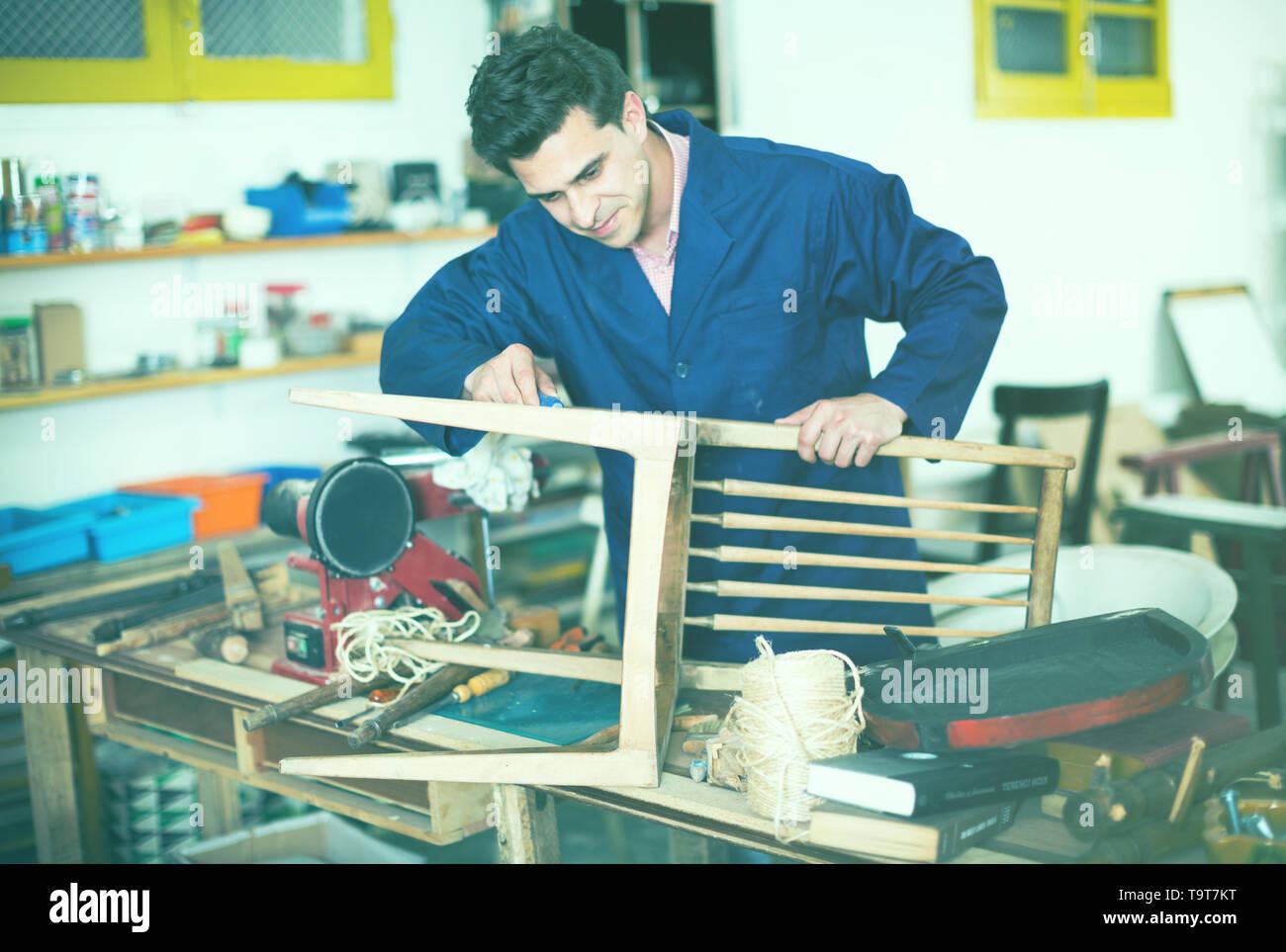 Carpenter working in repair studio and repairing broken wooden furniture - Stock Image
