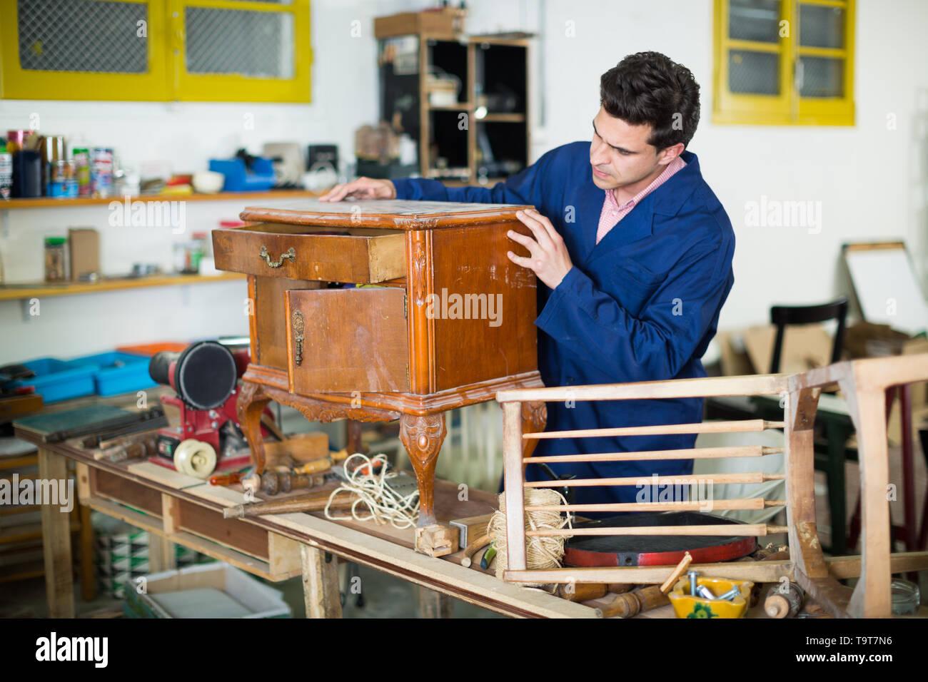Adult craftsman inspecting old nightstand before restoration in workshop - Stock Image