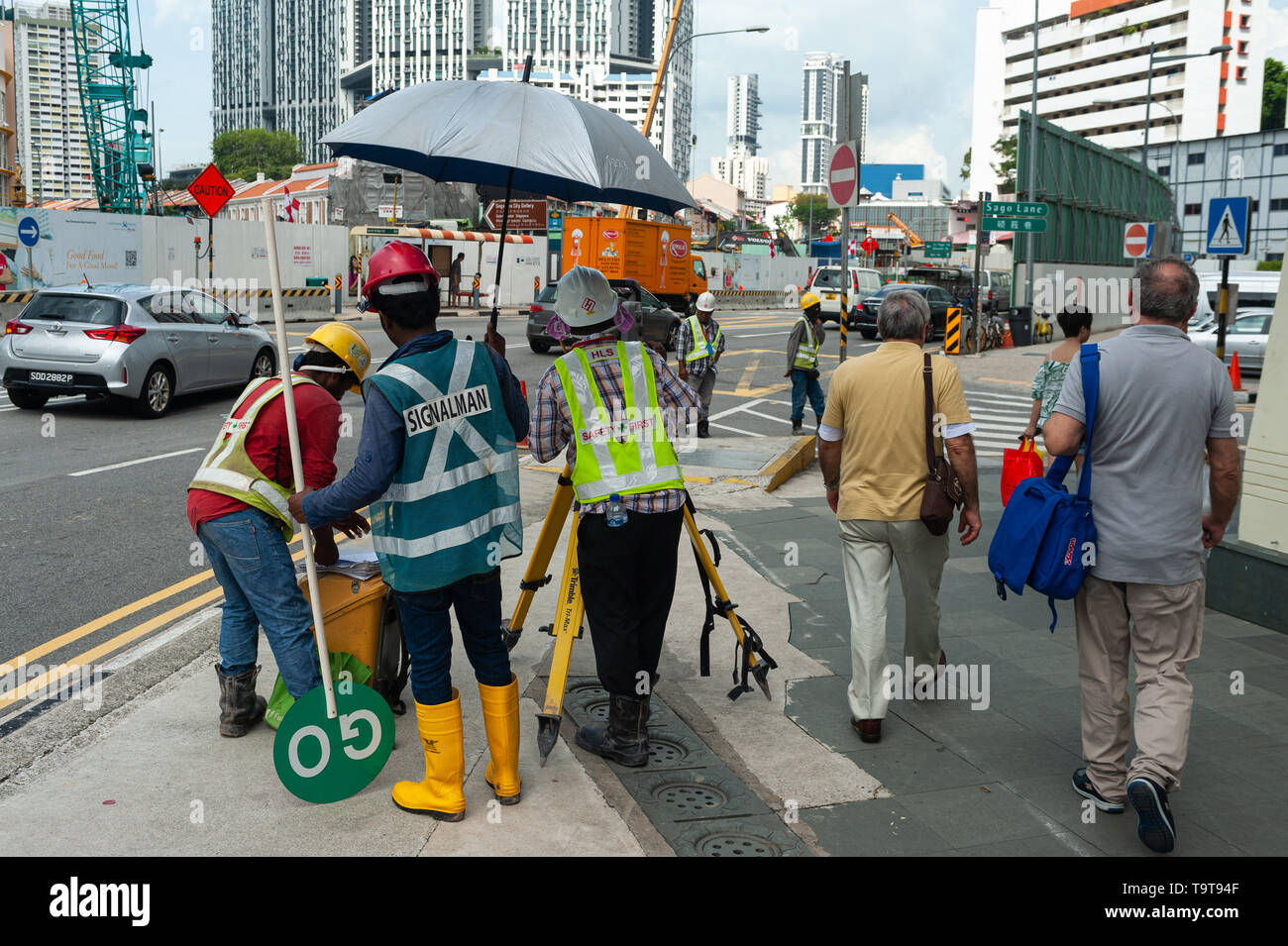 18.04.2018, Singapore, Republic of Singapore, Asia - A surveyor is taking readings from a theodolite in Chinatwon as people are walking by. - Stock Image