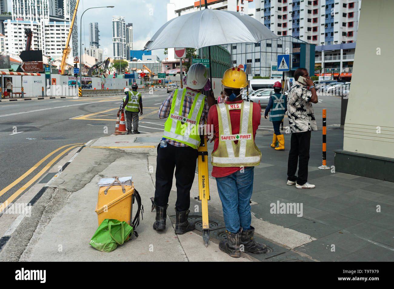 18.04.2018, Singapore, Republic of Singapore, Asia - A surveyor is taking readings from a theodolite in Chinatwon. - Stock Image