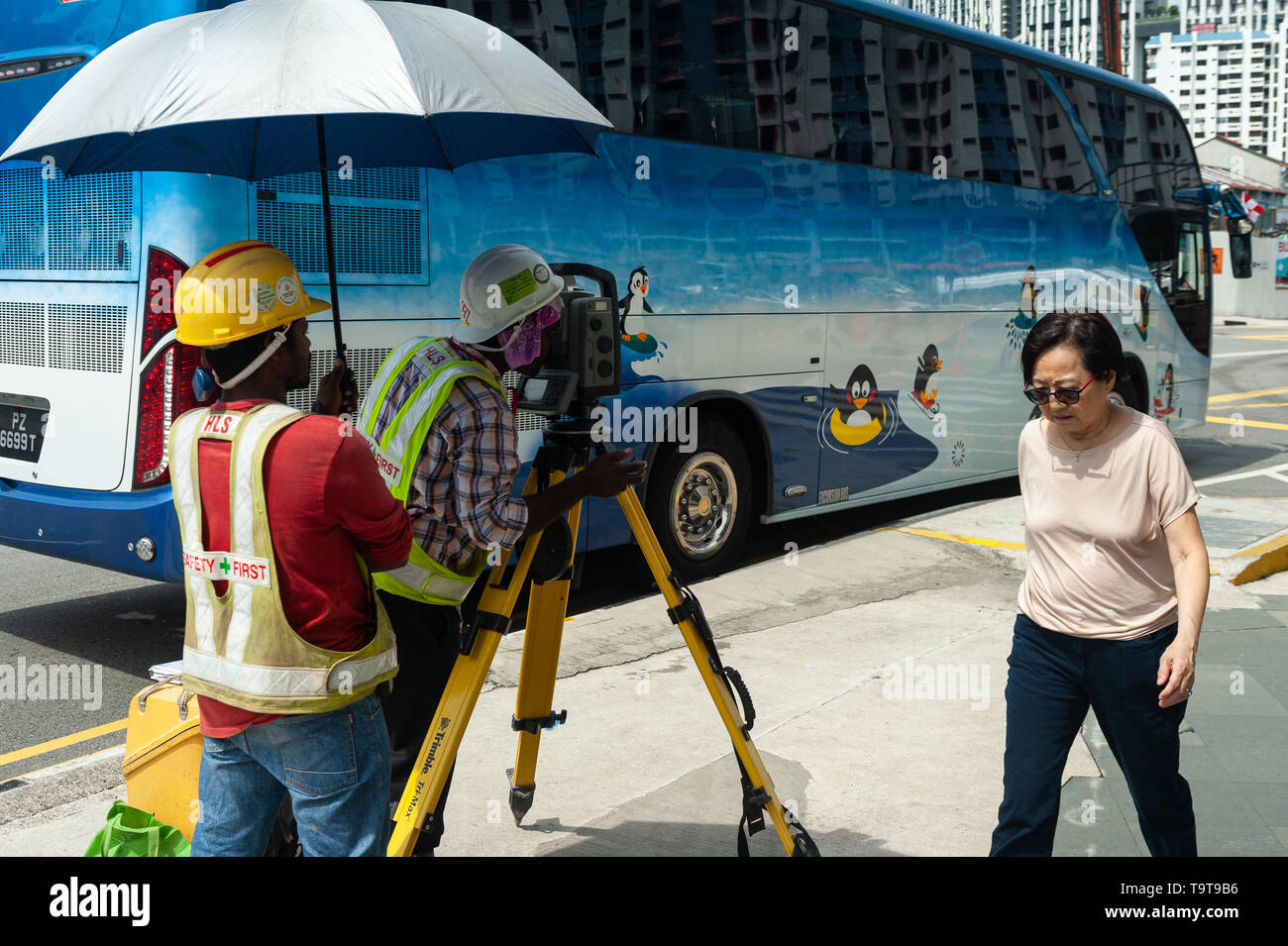 18.04.2018, Singapore, Republic of Singapore, Asia - A surveyor is taking readings from a theodolite in Chinatwon as a woman is walking by. - Stock Image