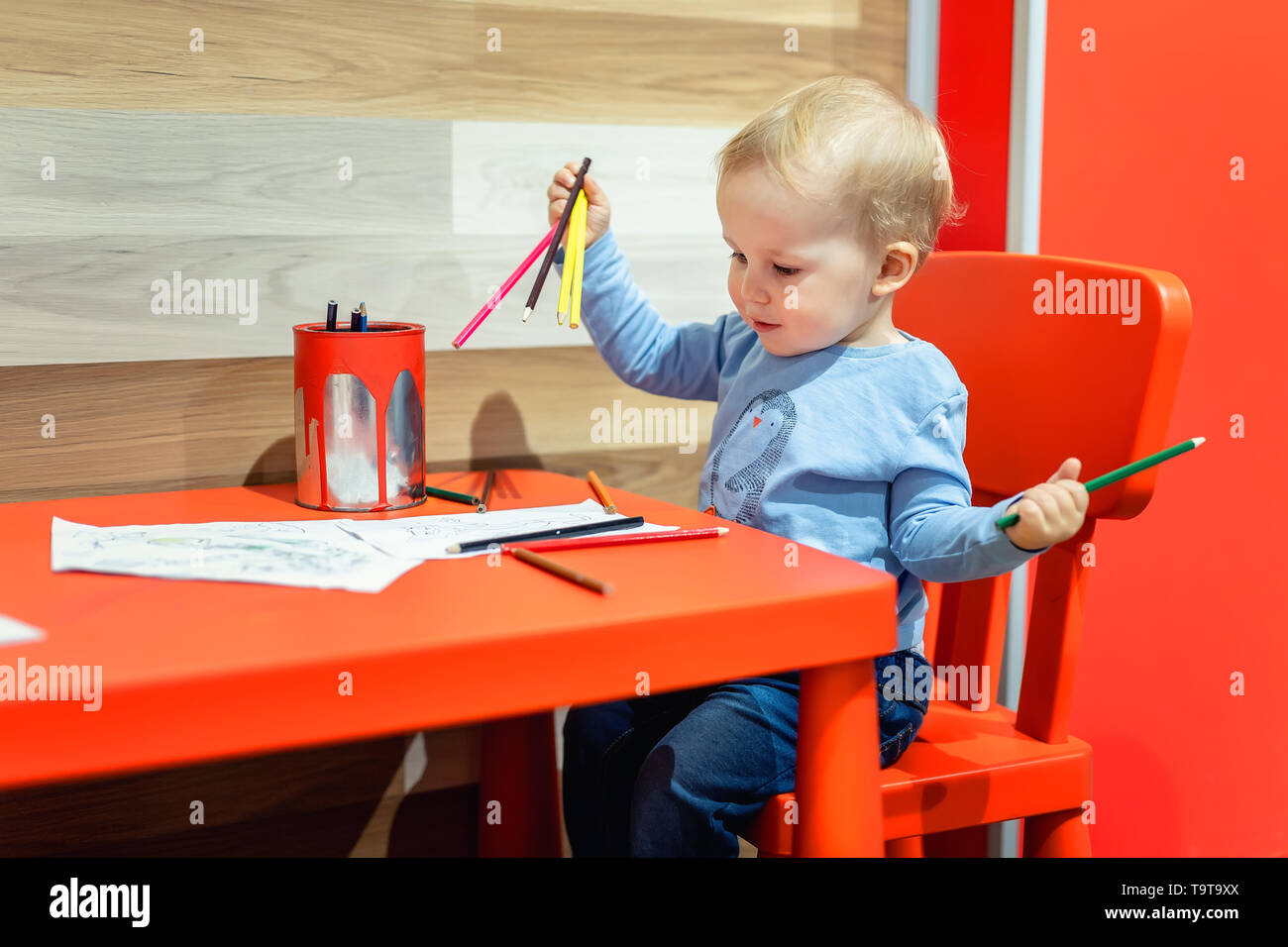 8cfb9f1a7cf4 Cute little caucasian blond toddler boy sitting at table and drawing at children  area at retail