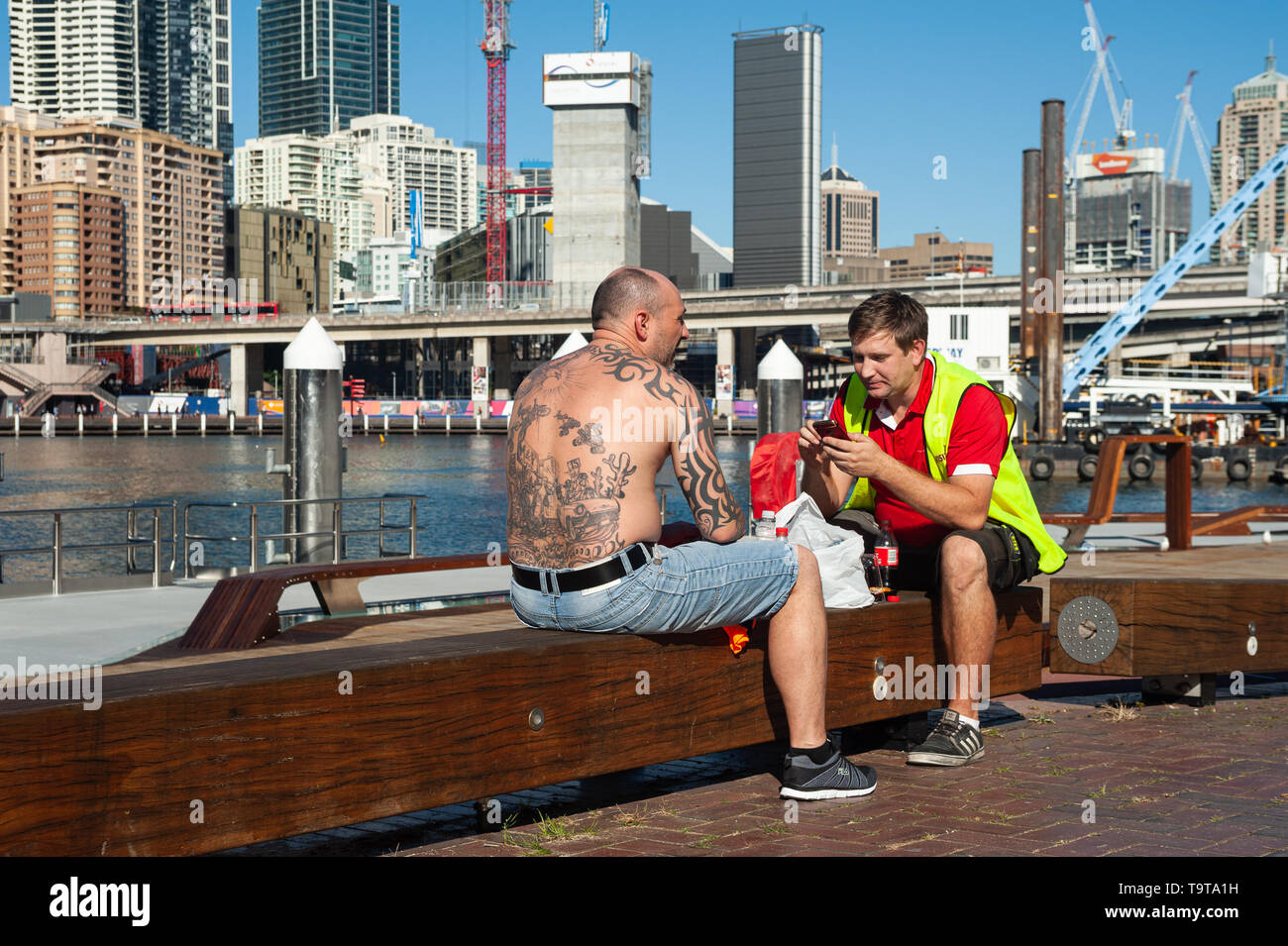 07.05.2018, Sydney, New South Wales, Australia - Two workers are taking their lunch break in Darling Harbour with the city skyline of the central busi - Stock Image