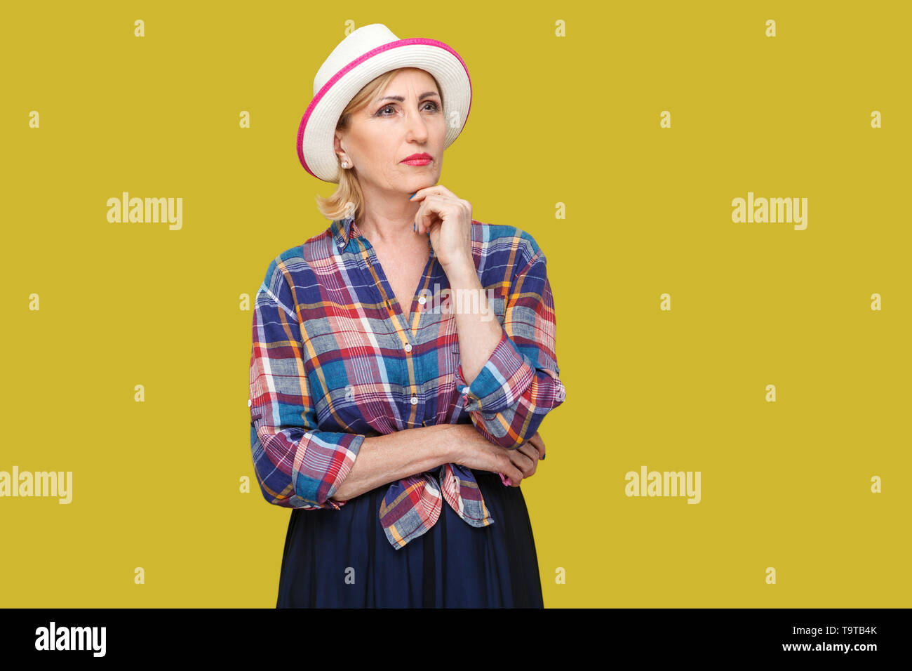 Portrait of serious thoughtful modern stylish mature woman in casual style with white hat standing, touching her chin, query and thinking what to do.  - Stock Image