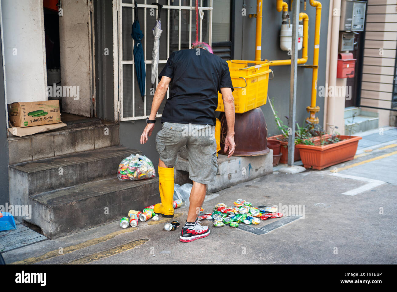 15.03.2019, Singapore, Republic of Singapore, Asia - A man in Chinatown is crushing empty beverage cans with a rubber boot. - Stock Image