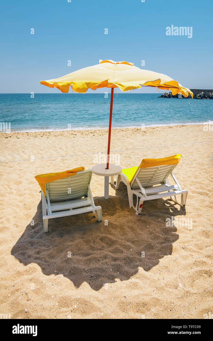 Beach umbrella on the sand beach. Concept for rest, relaxation, holidays, spa, resort - Stock Image