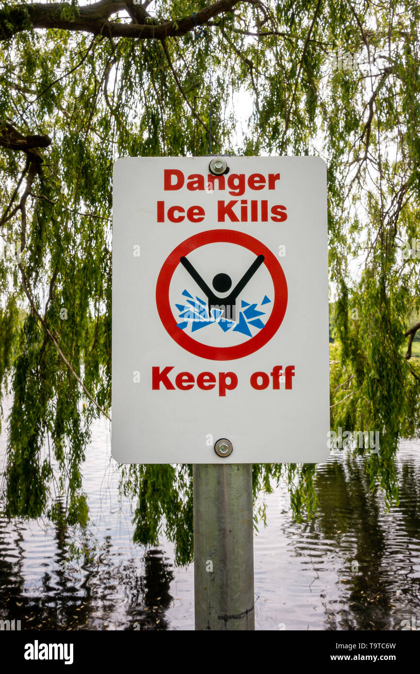 Danger ice kills keep off sign post on the bank of a small lake - Stock Image