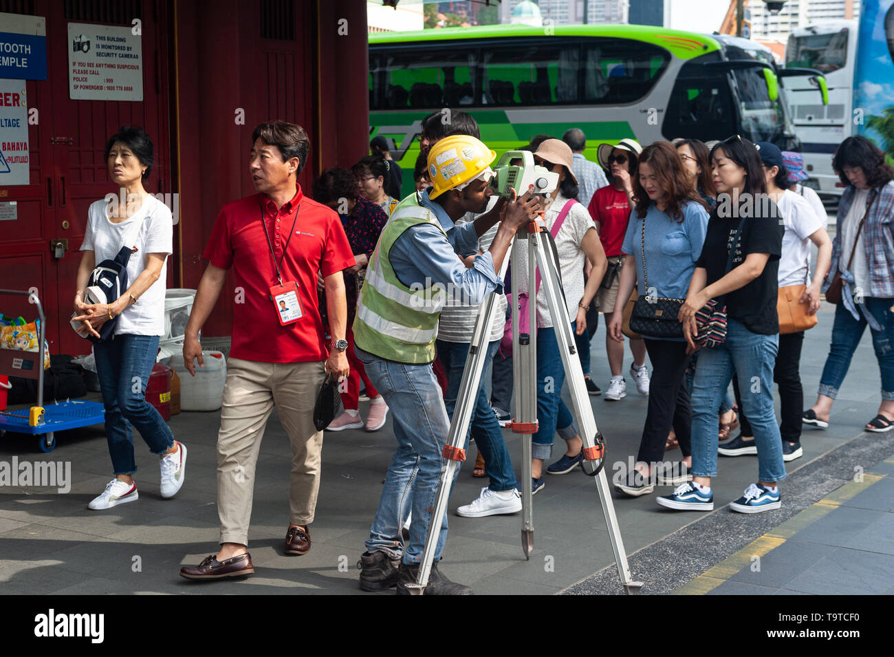 29.03.2019, Singapore, Republic of Singapore, Asia - A surveyor is taking readings from a theodolite as a group of tourists is passing by at the Buddh - Stock Image