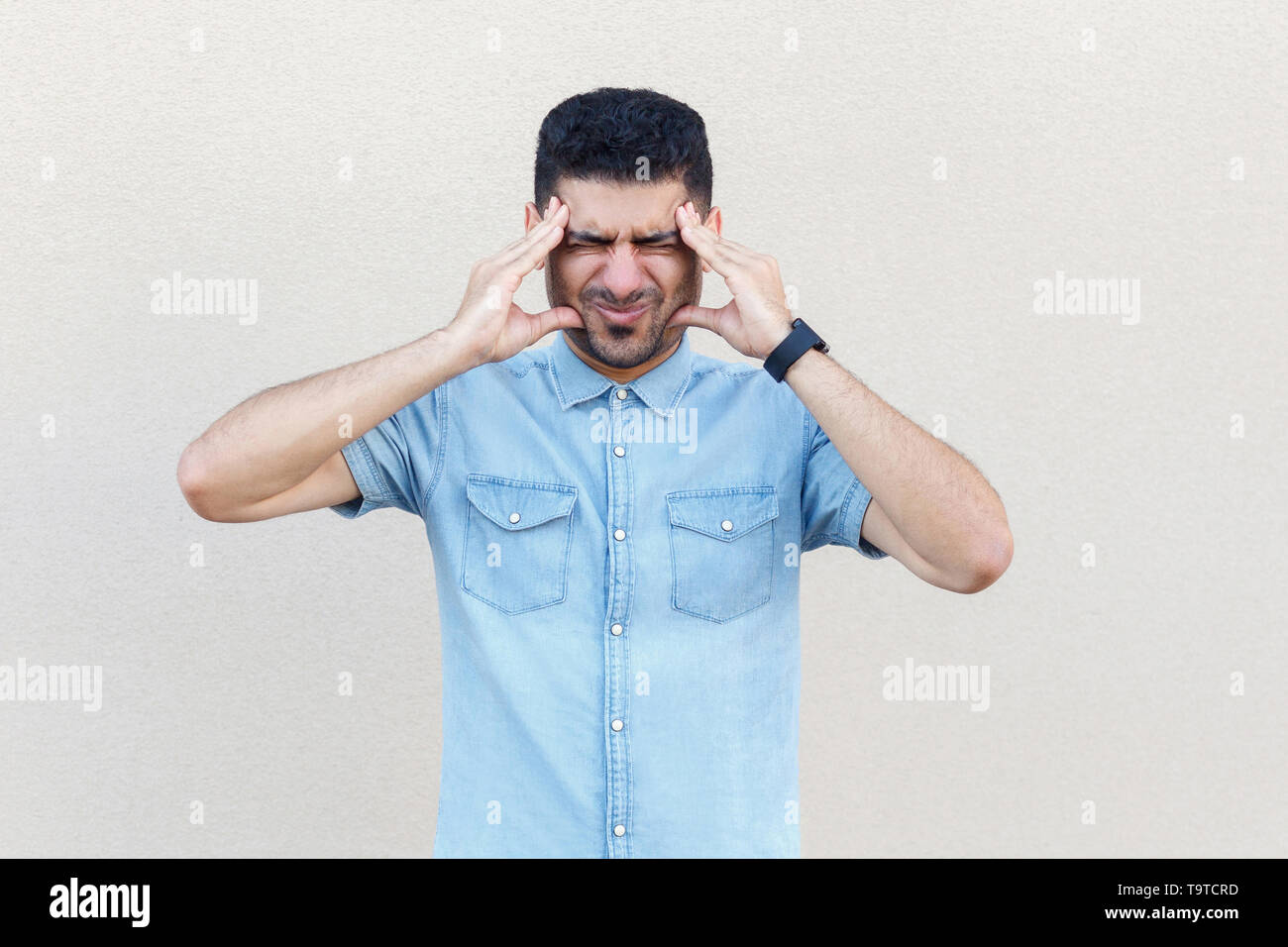 headache, confusion or problem. Portrait of sick handsome young bearded man in blue shirt standing and holding his head and feeling bad. indoor studio - Stock Image