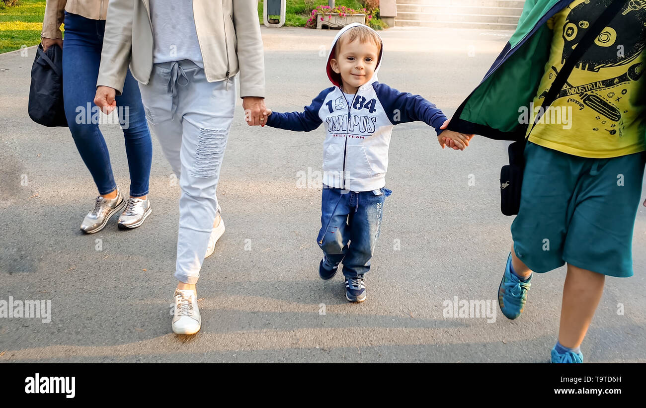 Photo of cute 3 years old toddler boy walking with his family in autumn park - Stock Image