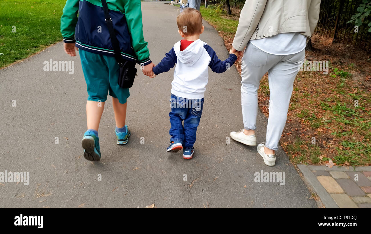 Photo of happy family with toddler boy holding by hands and walking in park - Stock Image