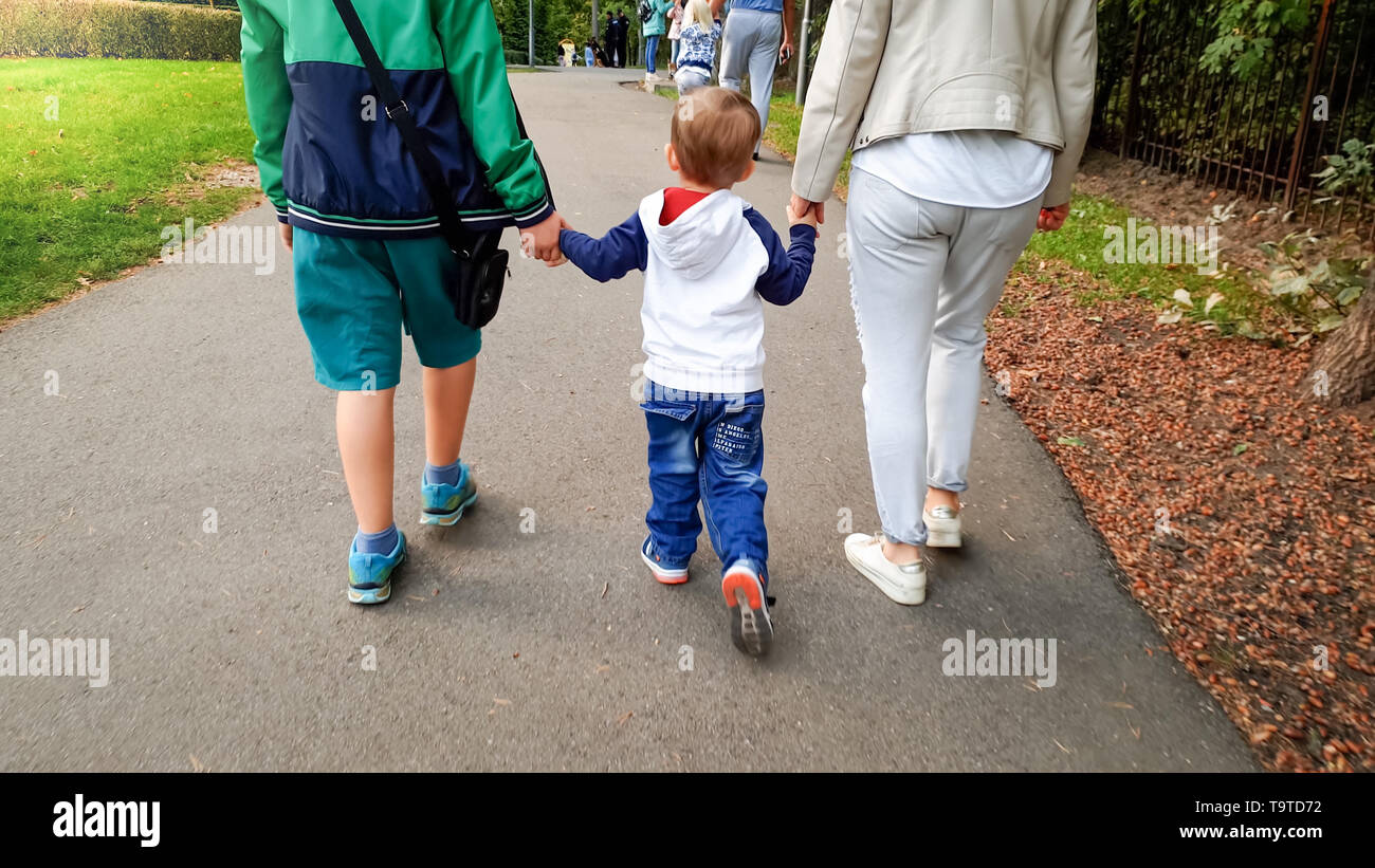 Photo of little toddler boy holding his mother and elder brother by hand and walking in autumn park - Stock Image