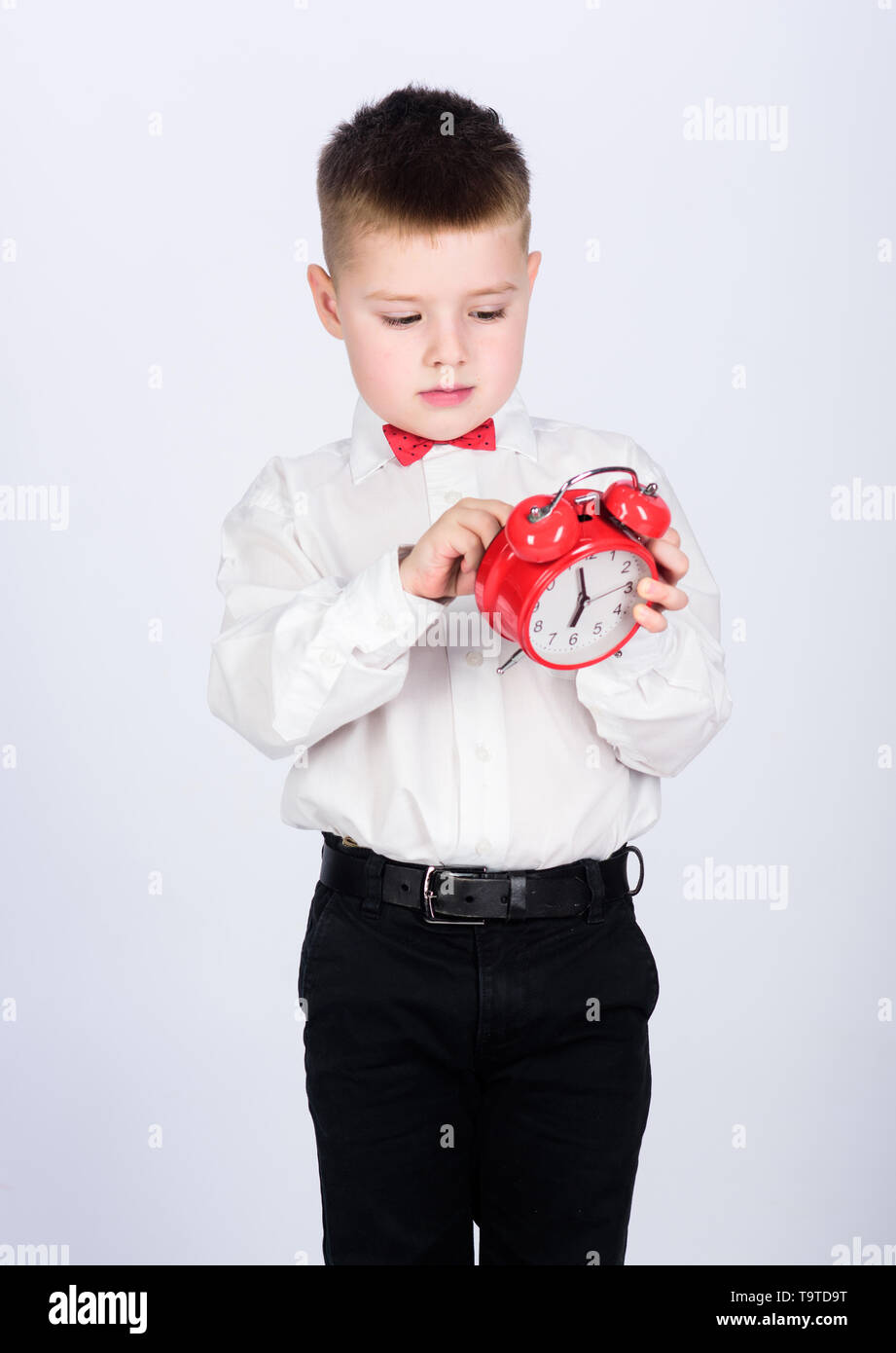 happy child with retro clock in bow tie. little boy with alarm clock. Time to relax. Party time. Businessman. Formal wear. Time management. Morning. t - Stock Image