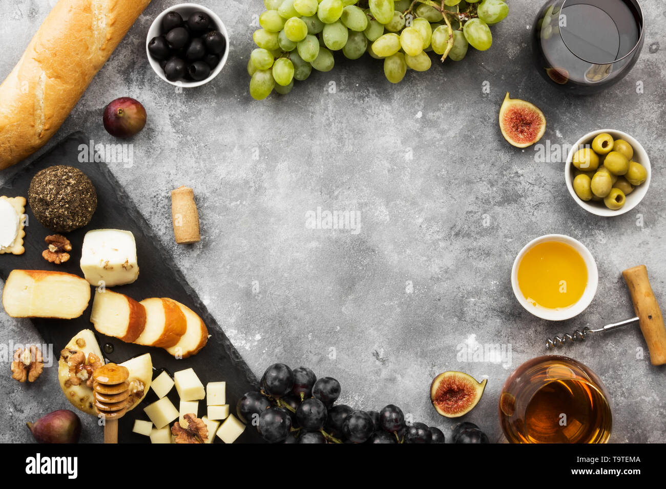 Snacks with wine - various types of cheeses, figs, nuts, honey, grapes, bread on a gray background. Top view, copy space. Food background Stock Photo