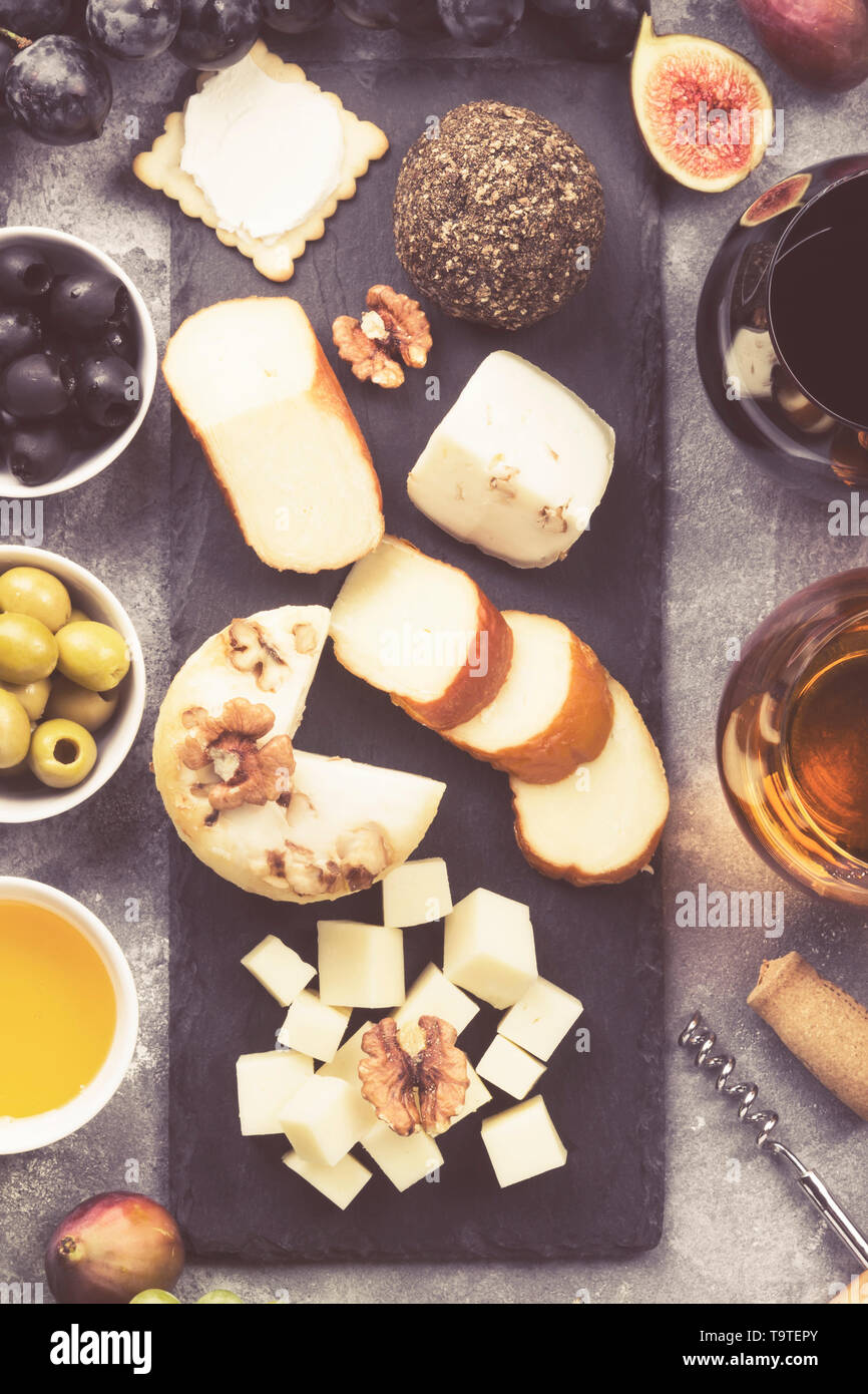 Snacks with wine - various types of cheeses, figs, nuts, honey, grapes on a gray background. Top view. Food background. Toned Stock Photo
