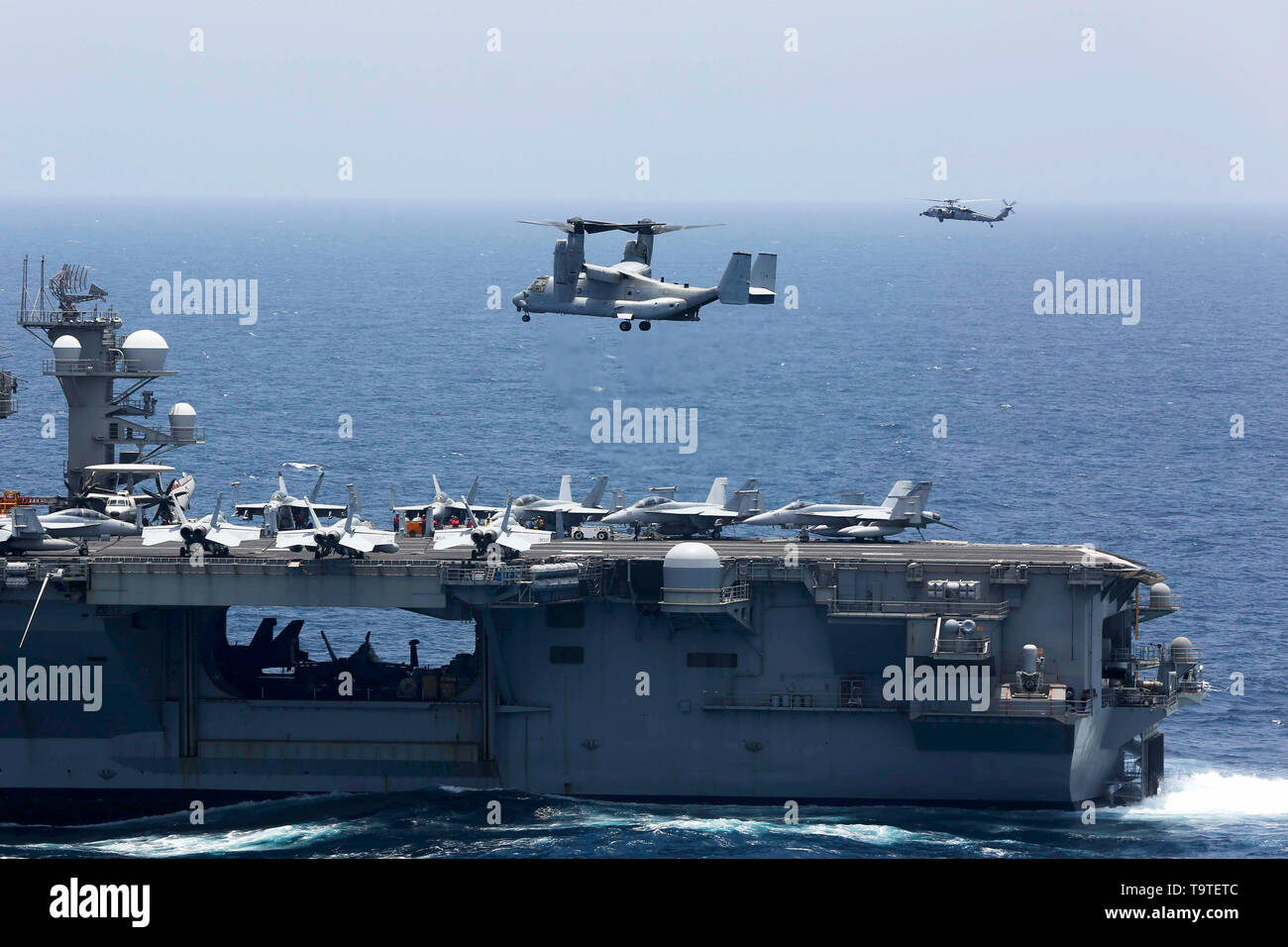 A U.S. Marine Corps MV-22 Osprey aircraft approaches the flight deck of the Nimitz-class aircraft carrier USS Abraham Lincoln to land during operations May 17, 2019 in the Arabian Sea. The joint strike group is part of additional forces being sent to the Middle East to counter what the Trump administration calls clear indications of threats from Iran. - Stock Image