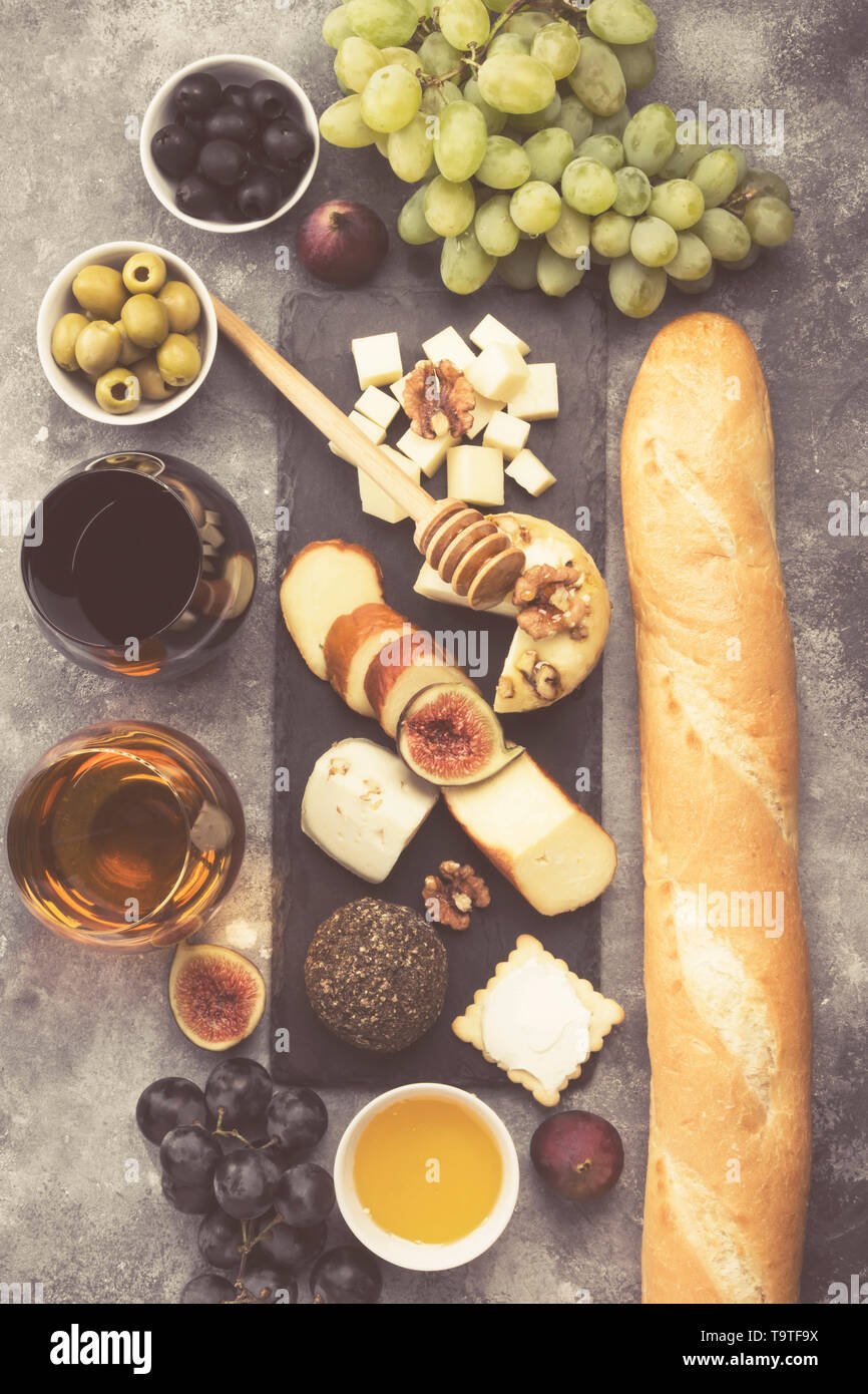 Snacks with wine - various types of cheeses, figs, nuts, honey, grapes, bread on a gray background. Top view. Food background. Toned Stock Photo