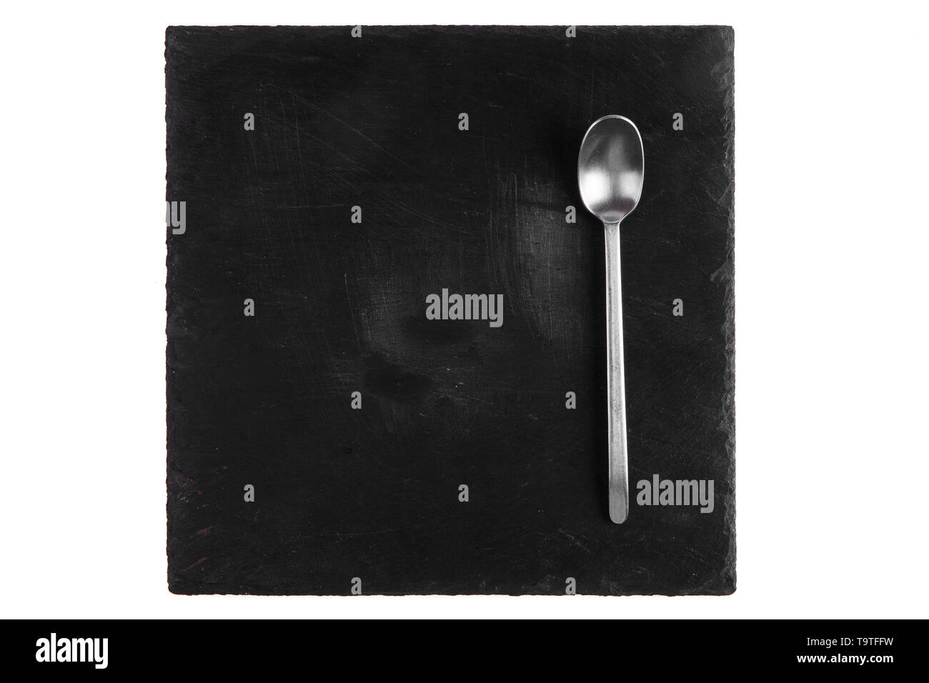 Drop of honey in a silver spoon and on a black stone tile - Stock Image