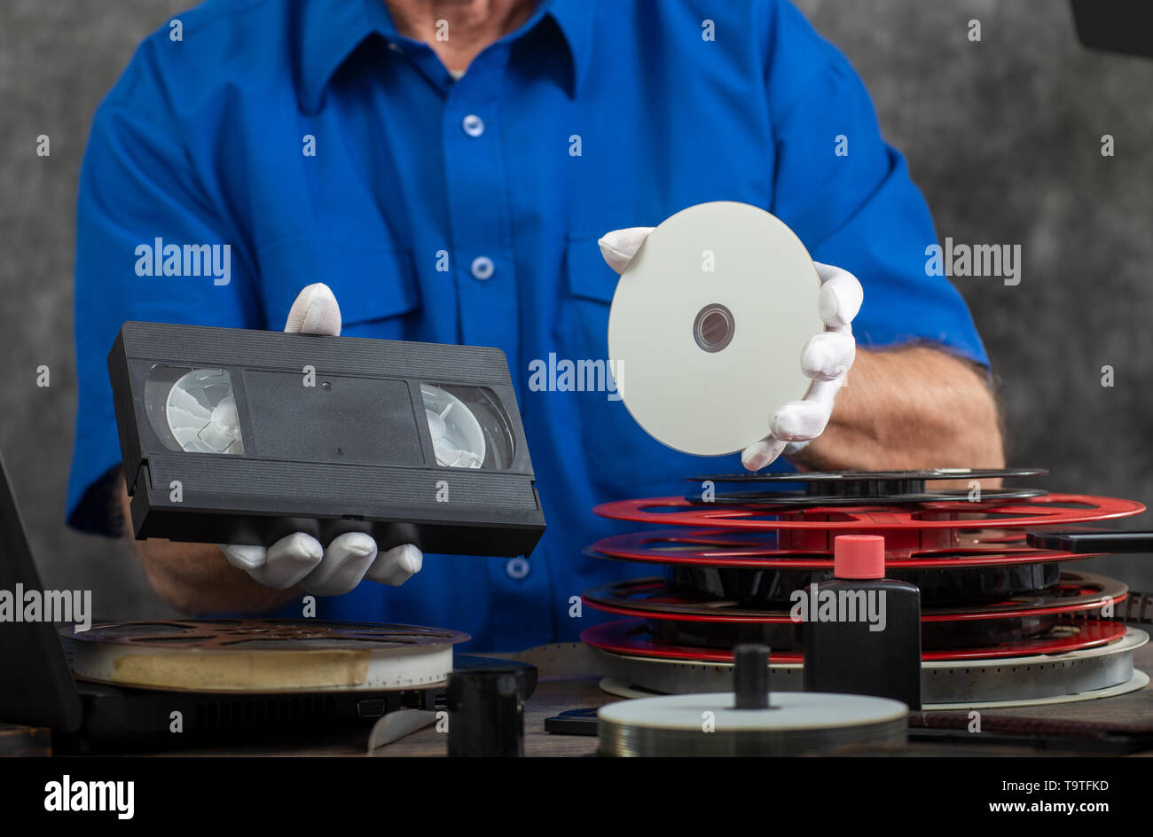 hand photographer holding a VHS tape and DVD disc for conversion - Stock Image