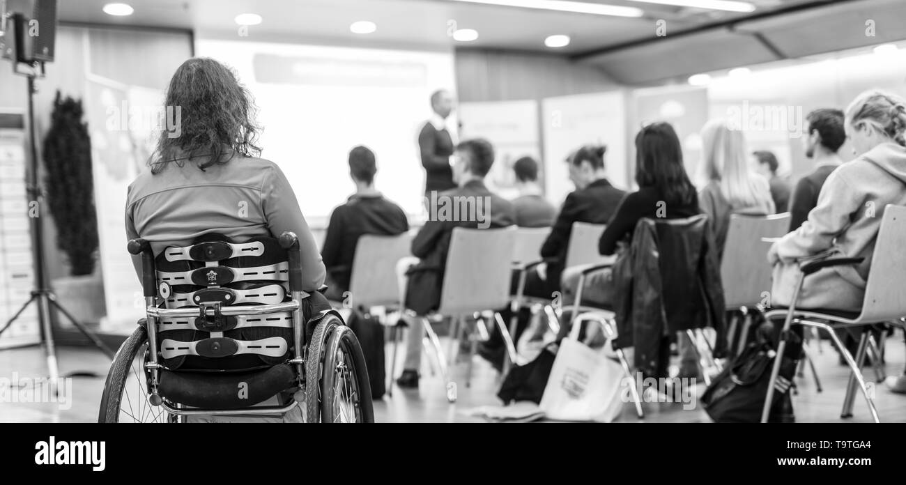 Rear view of unrecognizable woman on a wheelchair participating at business conference talk. - Stock Image