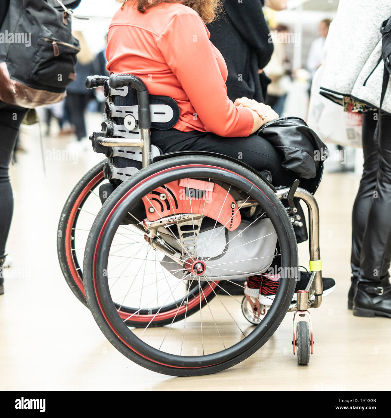 Close up of unrecognizable hanicapped woman on a wheelchair queuing in line to perform everyday tasks. - Stock Image