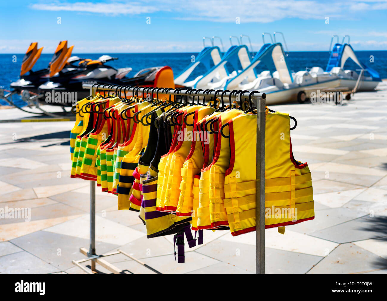 A lot of life jackets hanging on the beach. Water scooter and pedal boat in the background. The concept of water safety. - Stock Image