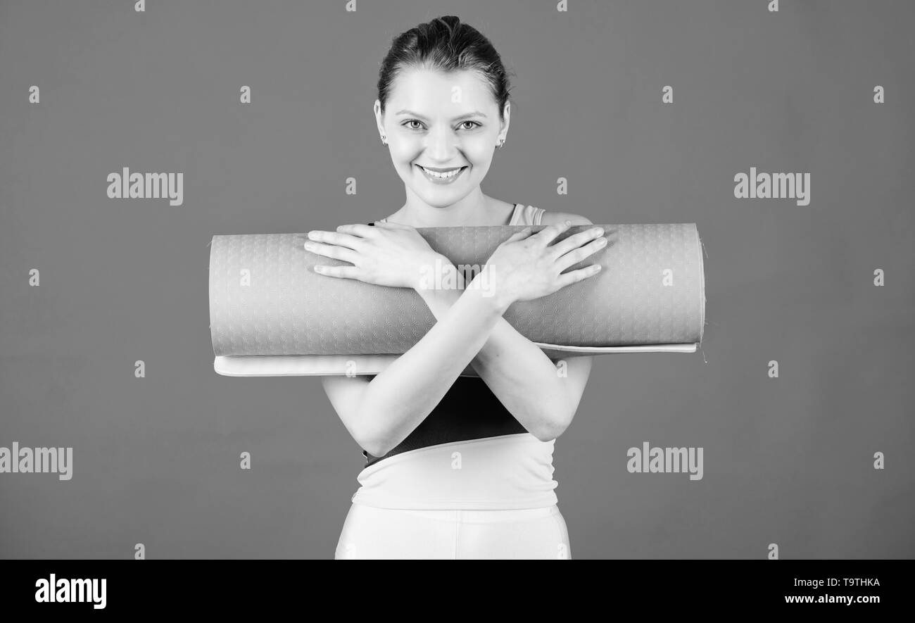 Girl smiling slim fit athlete hold fitness mat. Fitness and stretching. Stretching muscles. Getting into the yoga groove. Yoga as hobby and sport. Yog - Stock Image