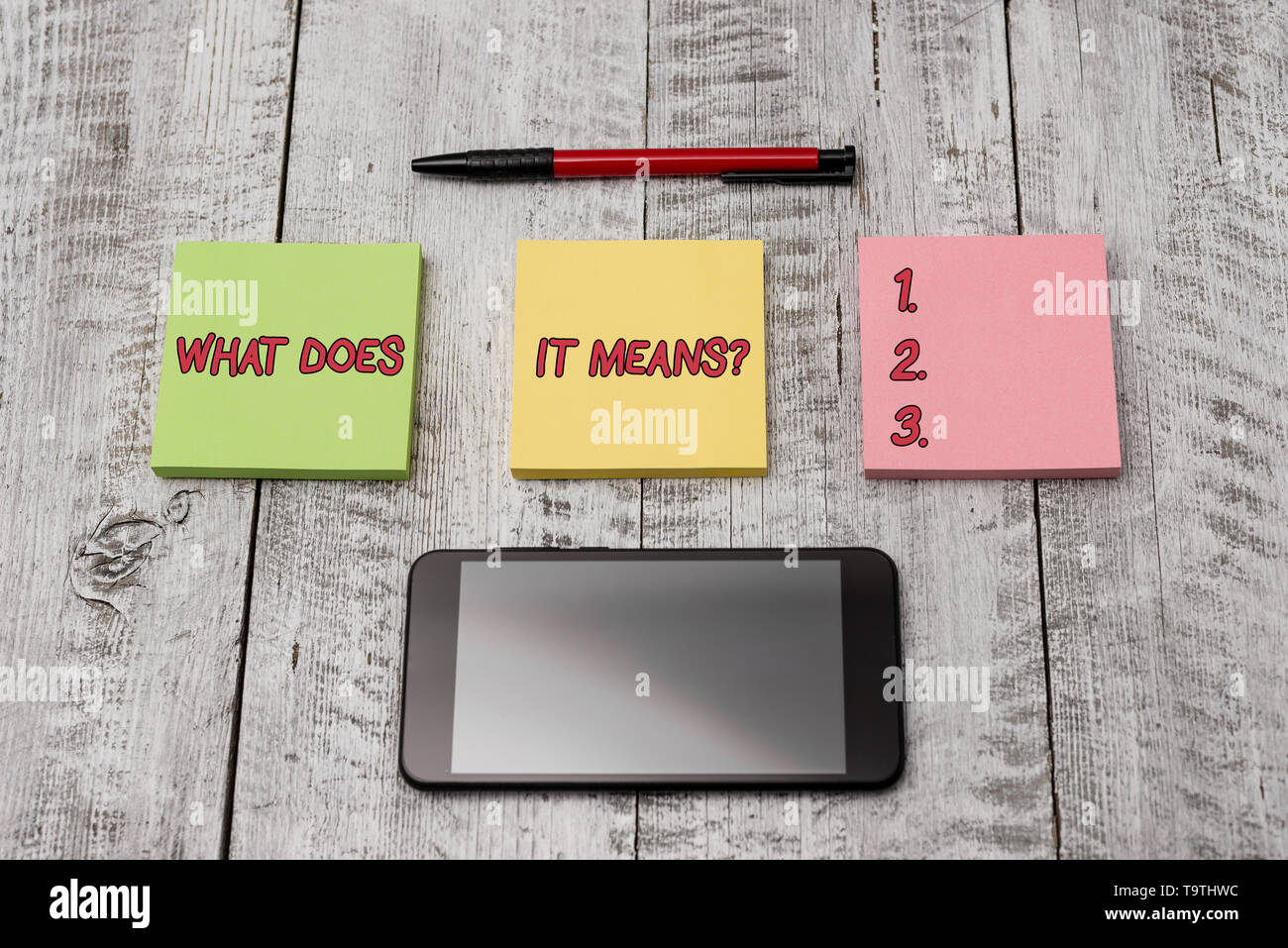 Writing note showing What Does It Means question. Business concept for asking meaning something said and do not understand Stationary equipment and ph - Stock Image
