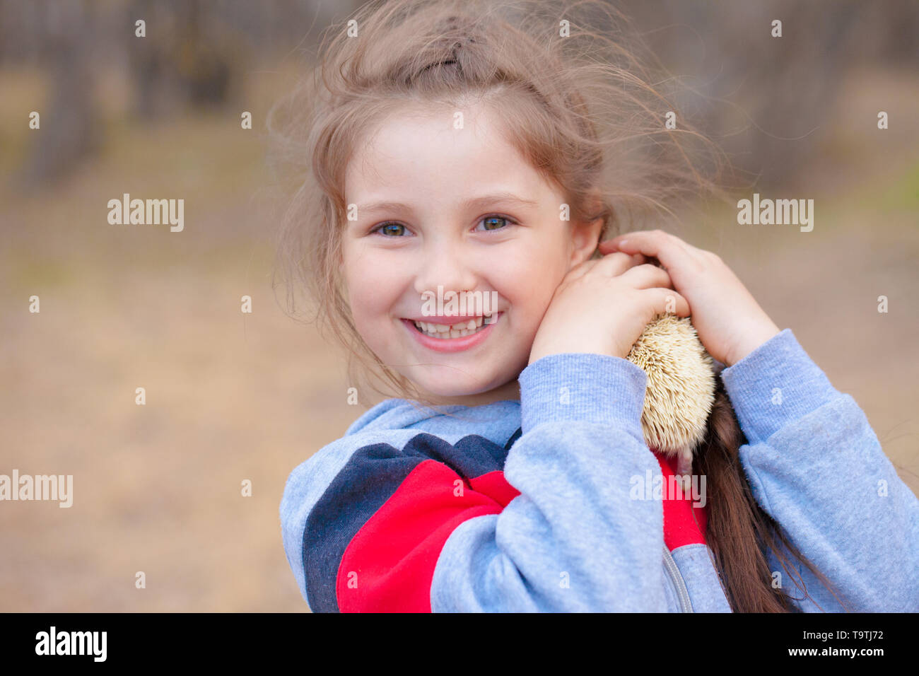 Smile concept. The girl laughs and plays with a hedgehog. The baby is holding a rodent. - Stock Image