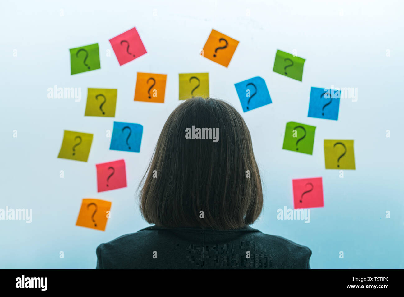 Businesswoman facing questions and challenges in business situation, rear view of female business person looking at question marks written on colorful - Stock Image