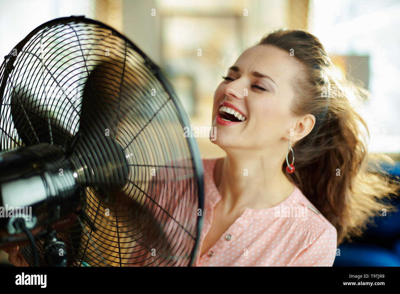smiling stylish housewife in the modern house in sunny hot summer day using electric floor standing fan. - Stock Image
