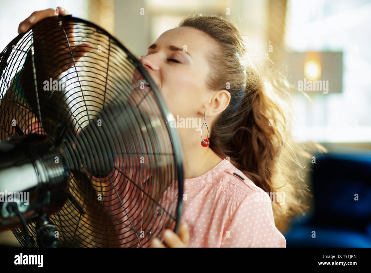 elegant woman at modern home in sunny hot summer day cooling down using electric floor standing fan. - Stock Image