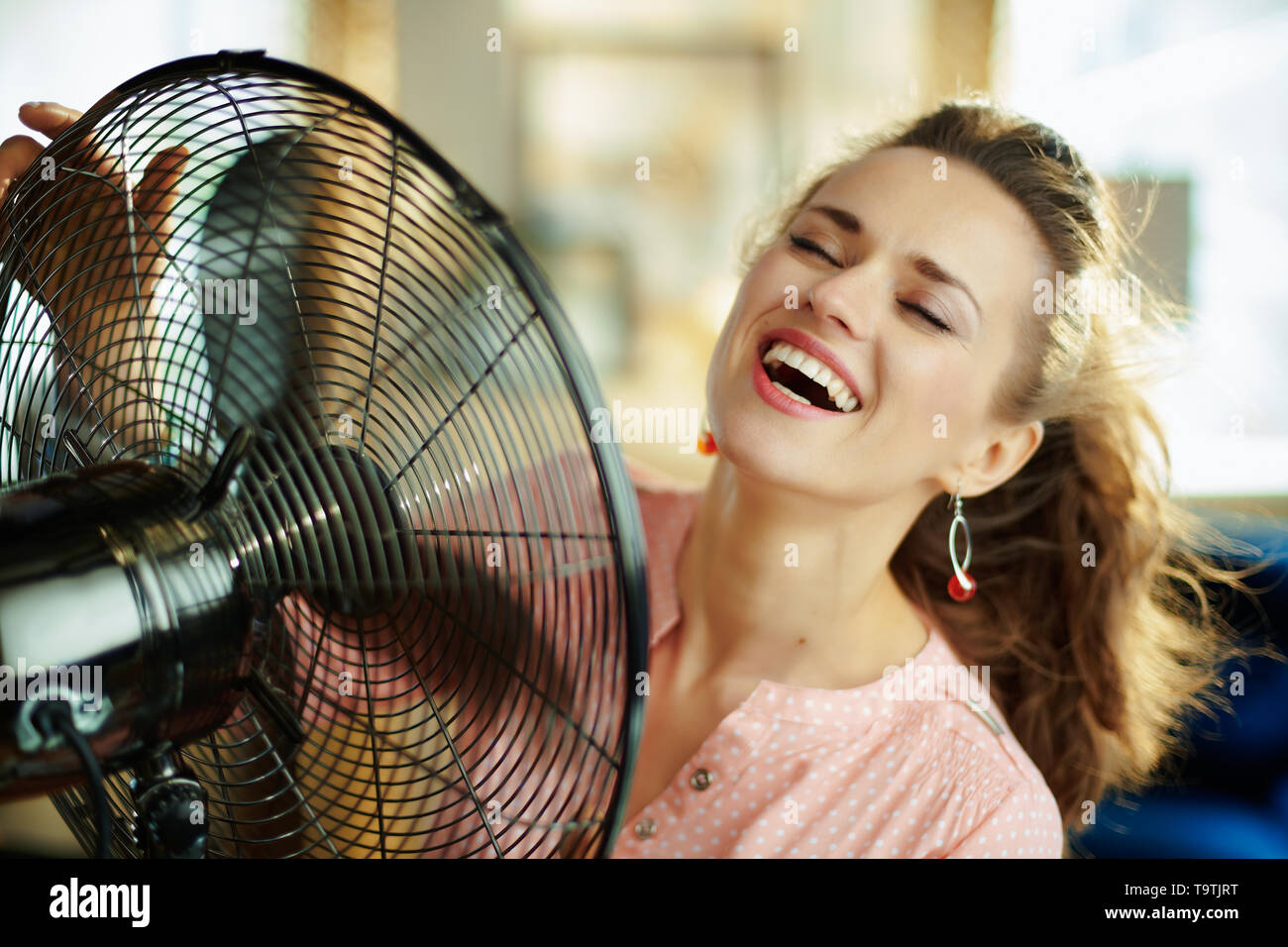 smiling stylish woman in the modern living room in sunny hot summer day using metallic floor standing fan. - Stock Image