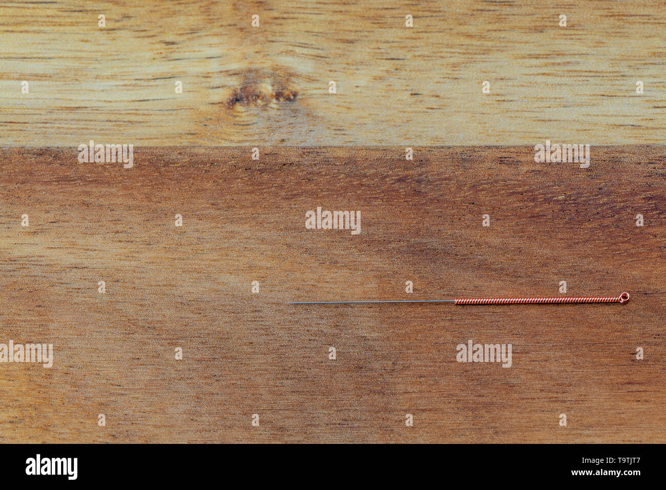 Traditional copper handle acupuncture needles for acupuncture and dry needling on a wood background - Stock Image