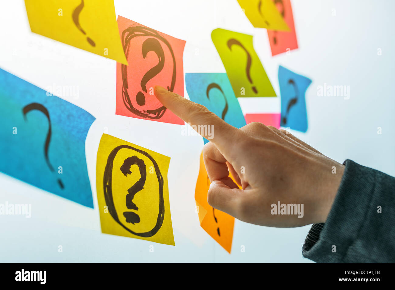 Businesswoman asking questions in business situation, female business person hand pointing to question marks written on colorful sticky note paper - Stock Image