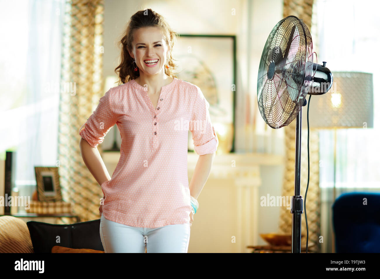 smiling elegant housewife at modern home in sunny hot summer day enjoying freshness in the front of fan. - Stock Image