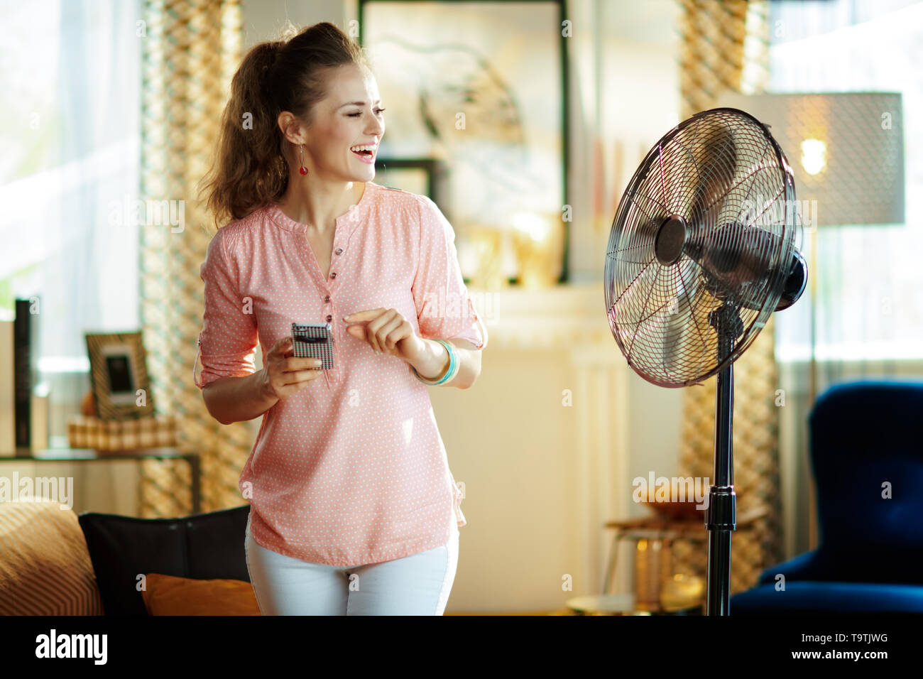 happy modern housewife in the modern house in sunny hot summer day using smart home app in smartphone to control fan. - Stock Image