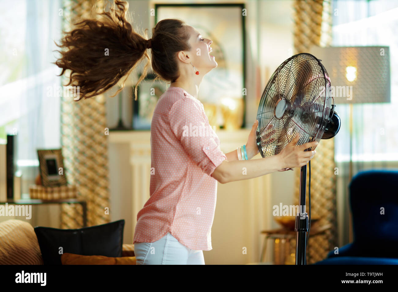 smiling modern housewife in the modern living room in sunny hot summer day enjoying fresh air in the front of working fan. - Stock Image