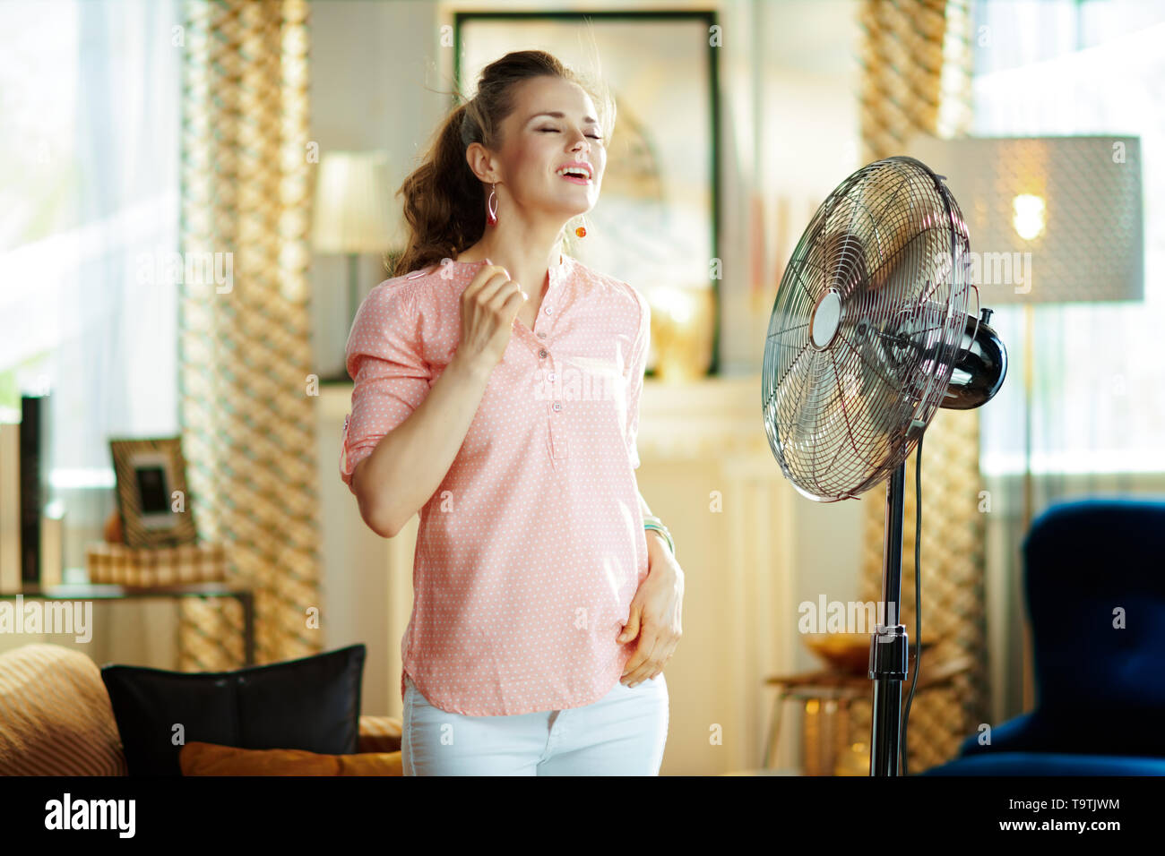 smiling modern woman in the modern house in sunny hot summer day enjoying freshness in the front of fan. - Stock Image