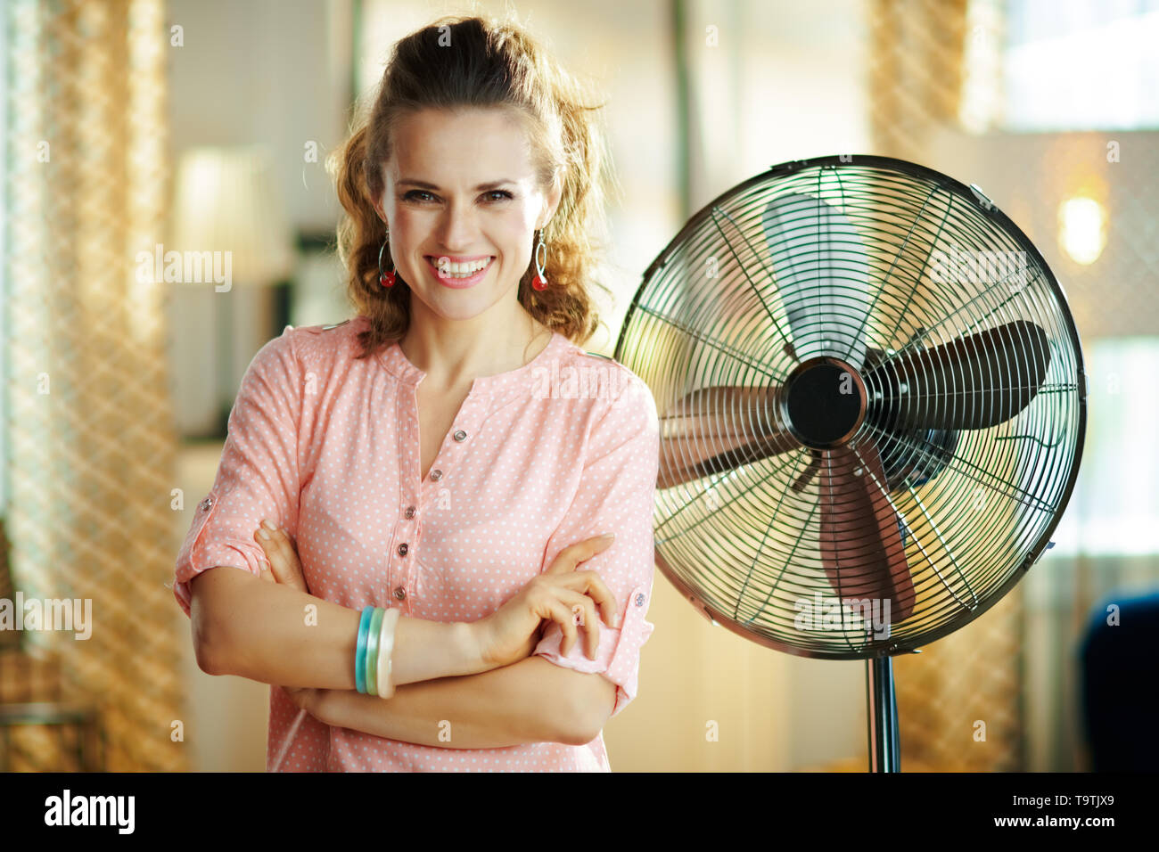 happy young woman in the modern house in sunny hot summer day near electric metallic fan. - Stock Image
