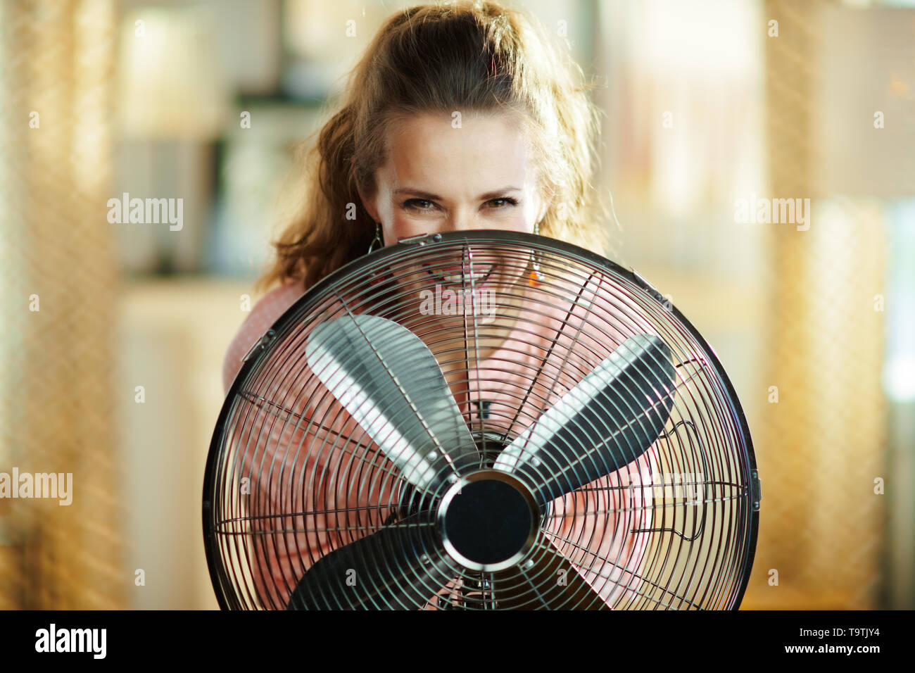 Portrait of smiling young woman in the modern house in sunny hot summer day looking out from electric metallic fan. - Stock Image