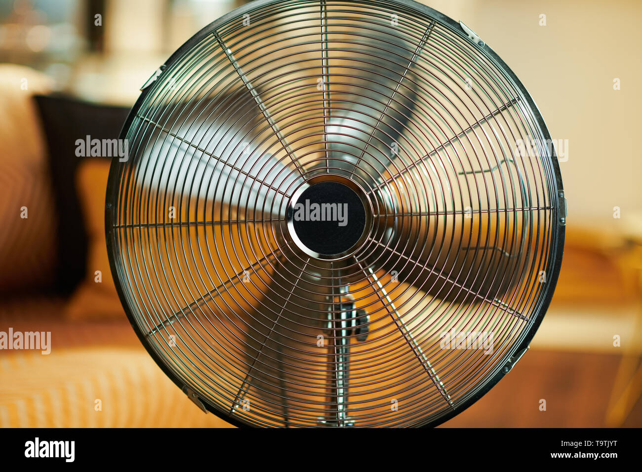 Closeup on working metallic floor standing fan at modern home in sunny hot summer day. - Stock Image