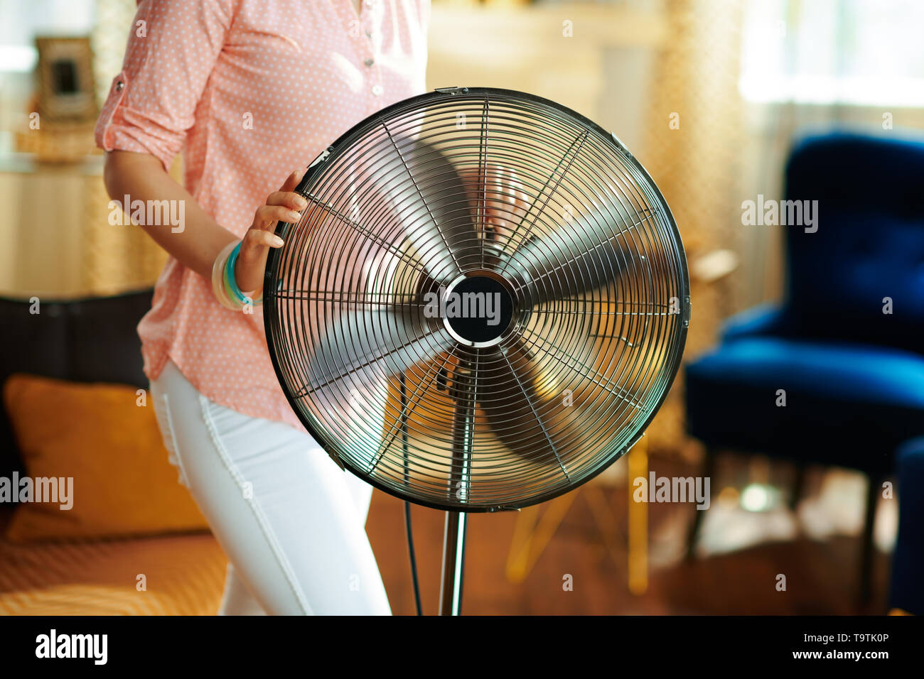Closeup on young housewife in the modern house in sunny hot summer day swtitching on metallic floor standing fan. - Stock Image