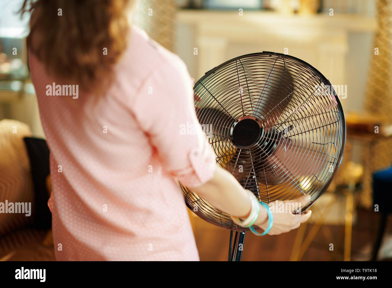 Seen from above stylish housewife at modern home in sunny hot summer day cooling down in the front of fan. - Stock Image