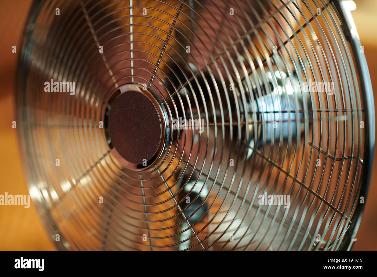 Closeup on working metallic floor standing fan in the modern house in sunny hot summer day. - Stock Image