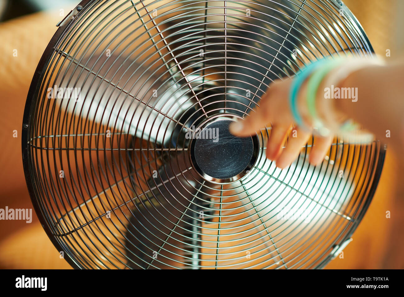 working metallic floor standing fan and female hand stretching to fan in the modern living room in sunny hot summer day. - Stock Image